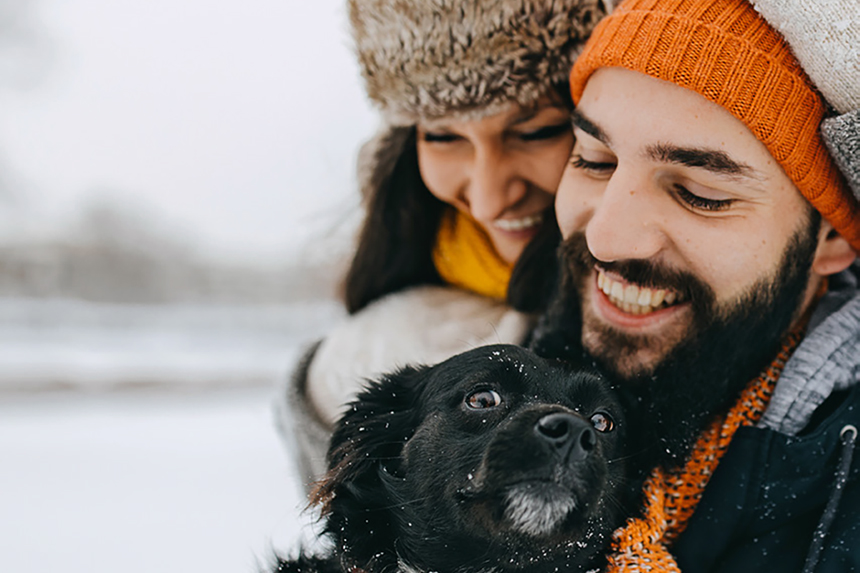 Couple in the snow play with dog