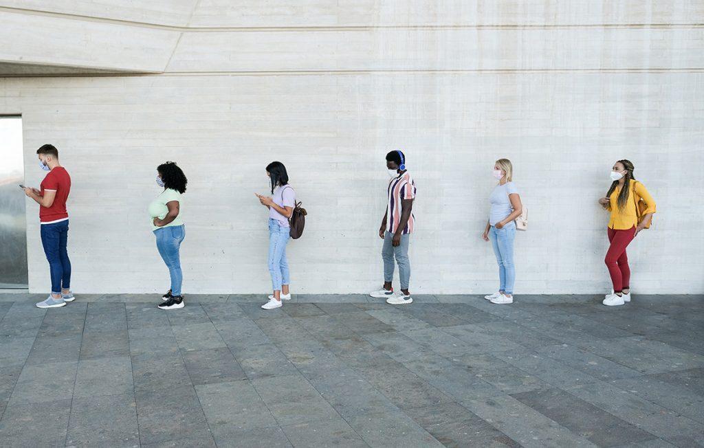 People in masks wait in a line alongside a building