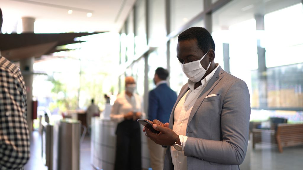 Mature man waiting for an elevator using mobile phone on office's lobby - with face mask