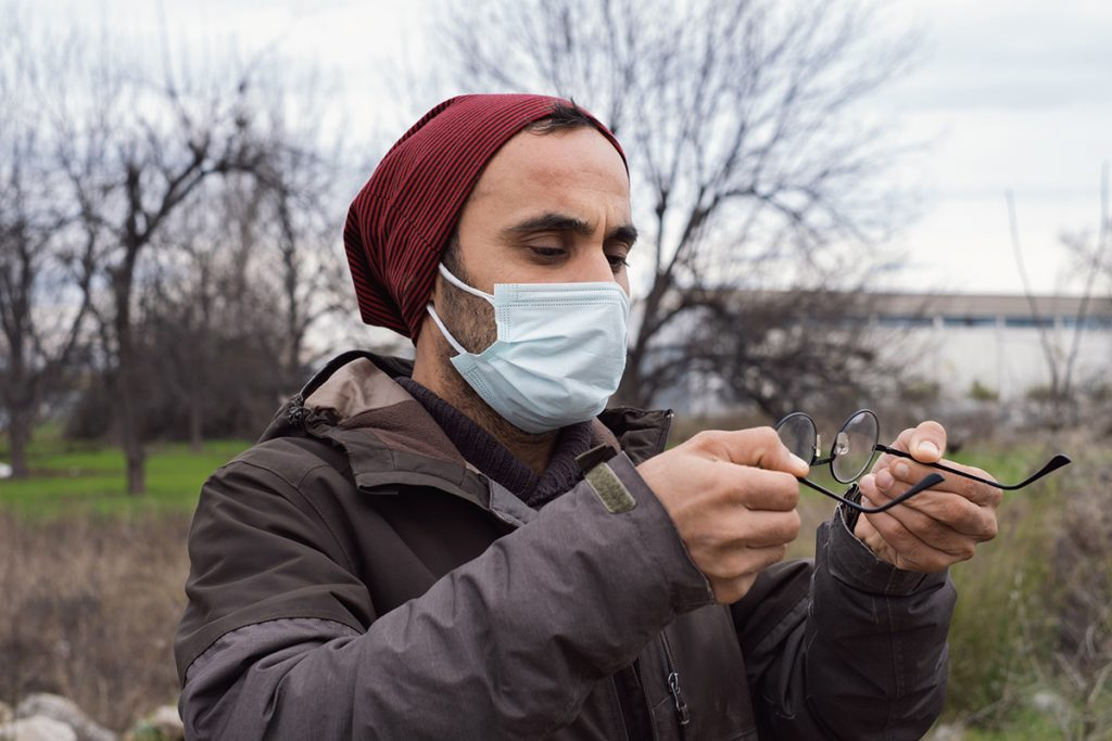Young man with misted glasses due to protective mask.