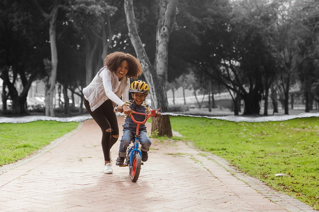 A woman helps her child ride a bike in the park