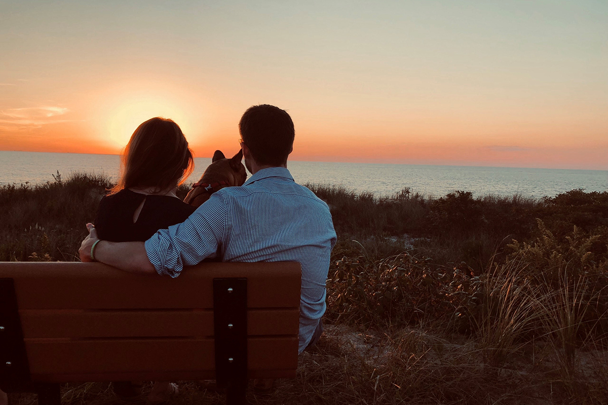 Two people looking at a sunset from a bench