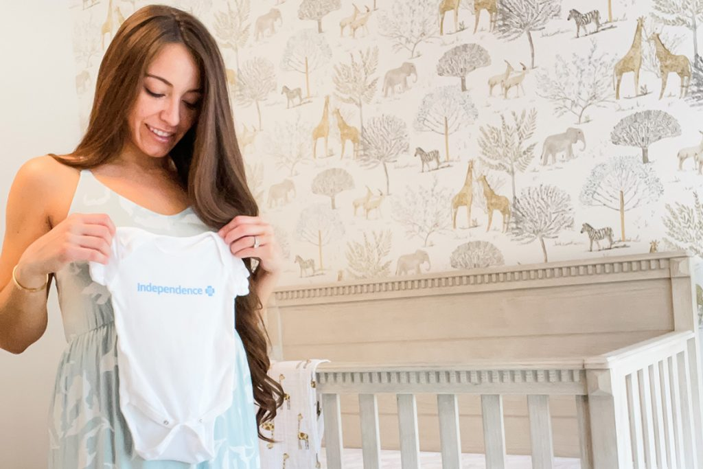 Monique Muldoon holds a onesie up next to a crib