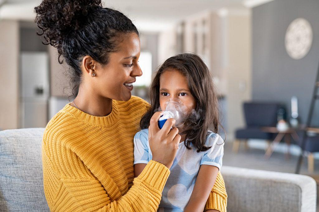 Mother helping child use nebulizer