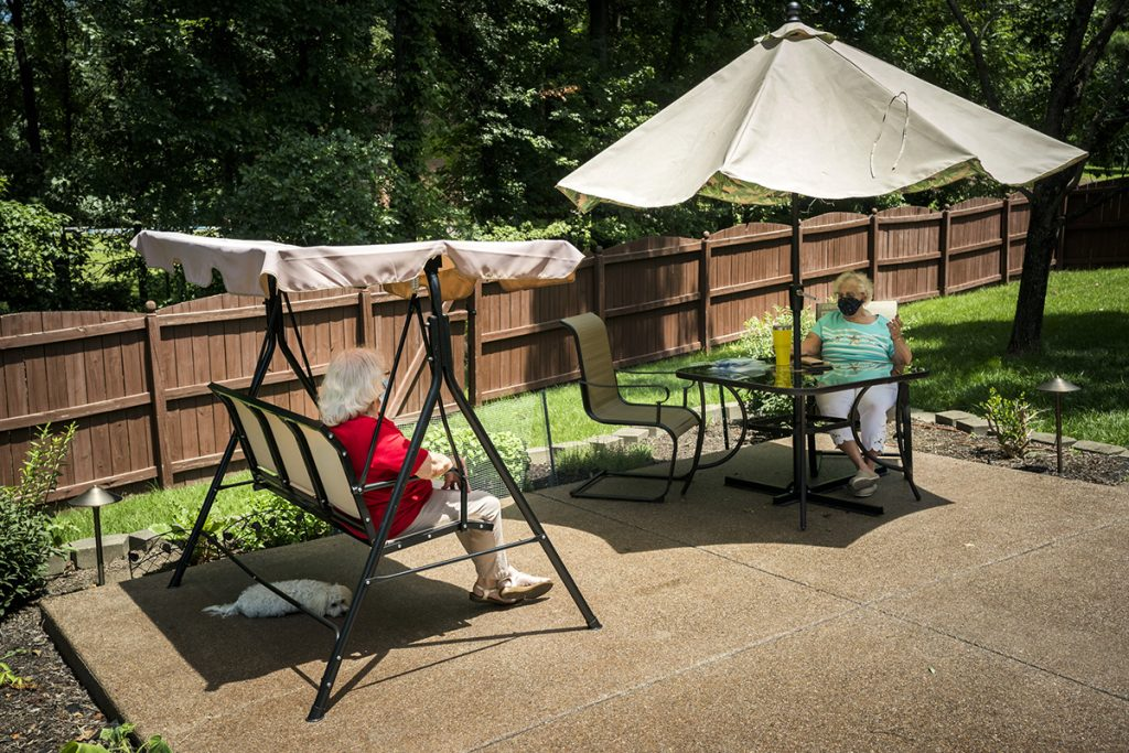 Two senior women in the backyard on a summer day, wearing face masks and social distancing