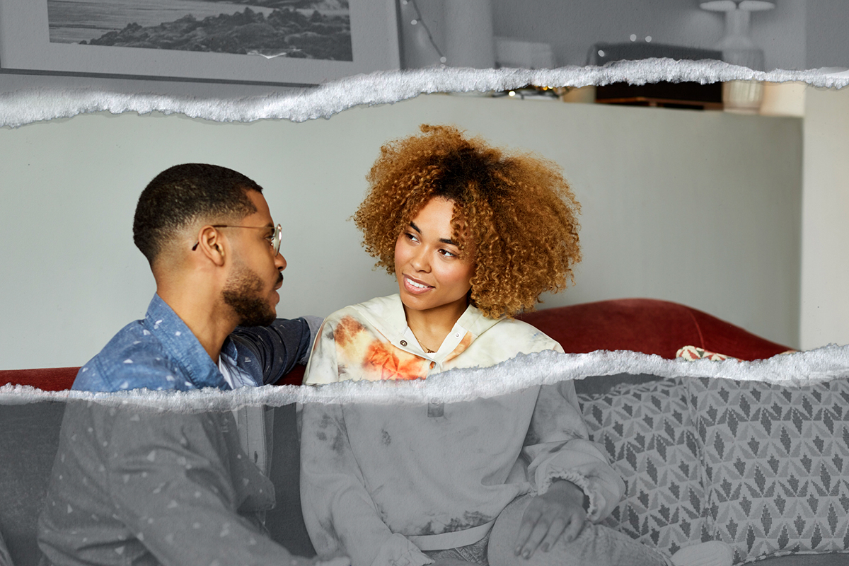 A couple discusses an issue in their living room.