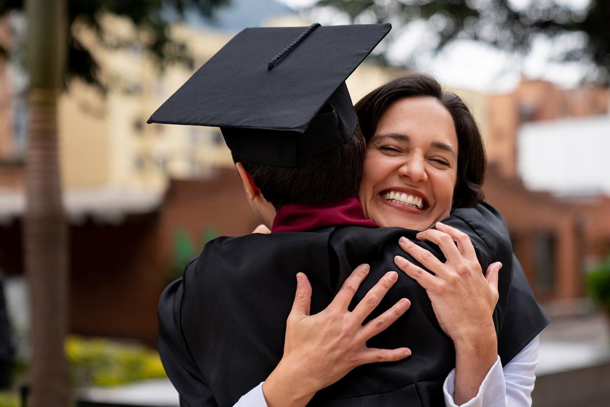 Proud mother hugging her college graduate
