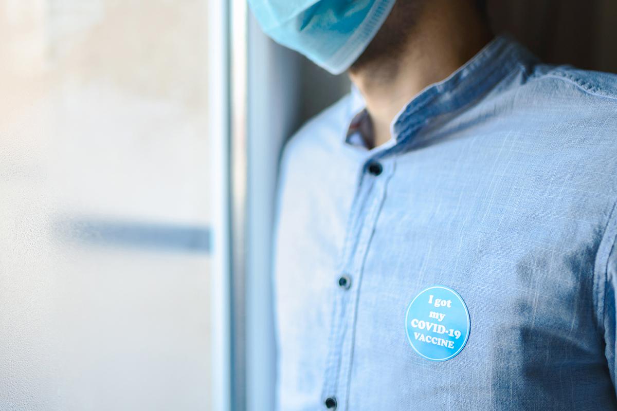 """Person with """"I got my COVID-19 vaccine"""" sticker."""