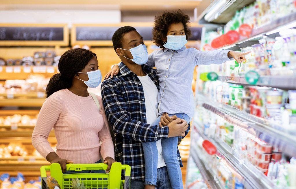 Family shopping at the supermarket wearing masks