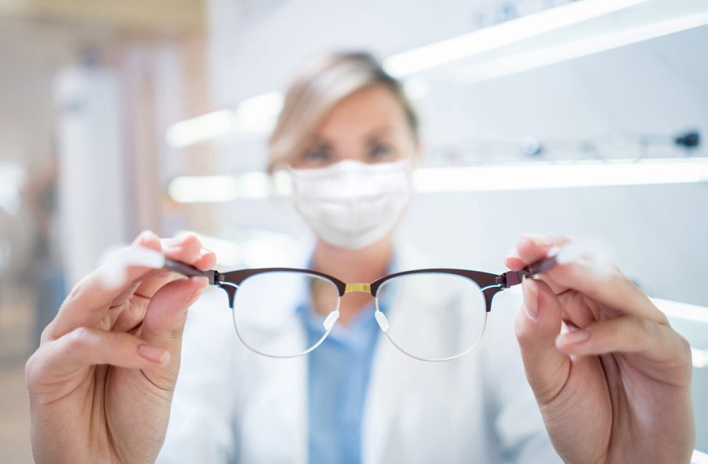 Optician holding glasses and wearing a facemask