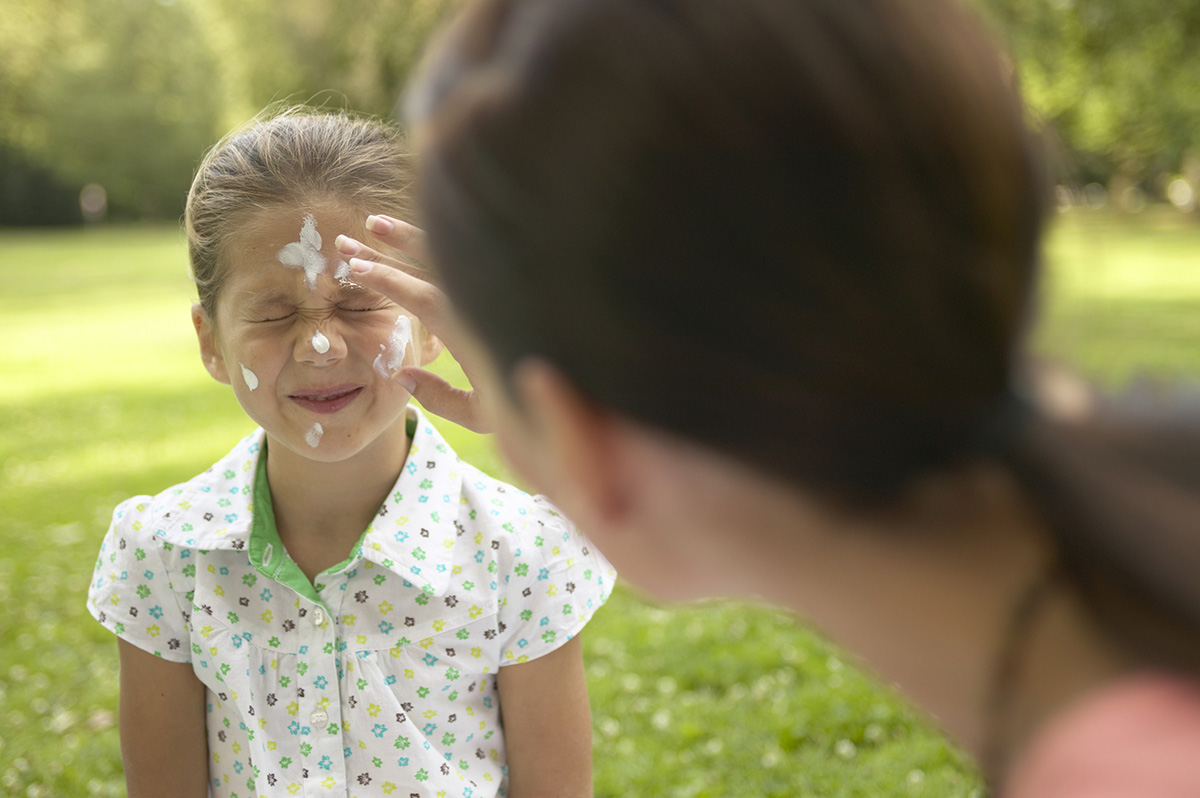 Mother applying sunscreen to daughter's face, outdoors
