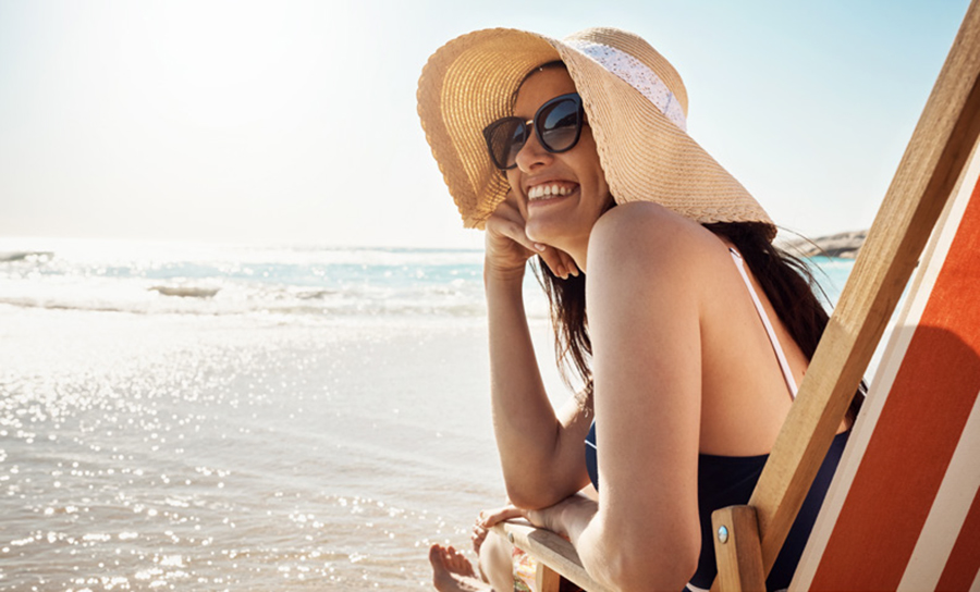 Shot of a woman relaxing on chair at the beach