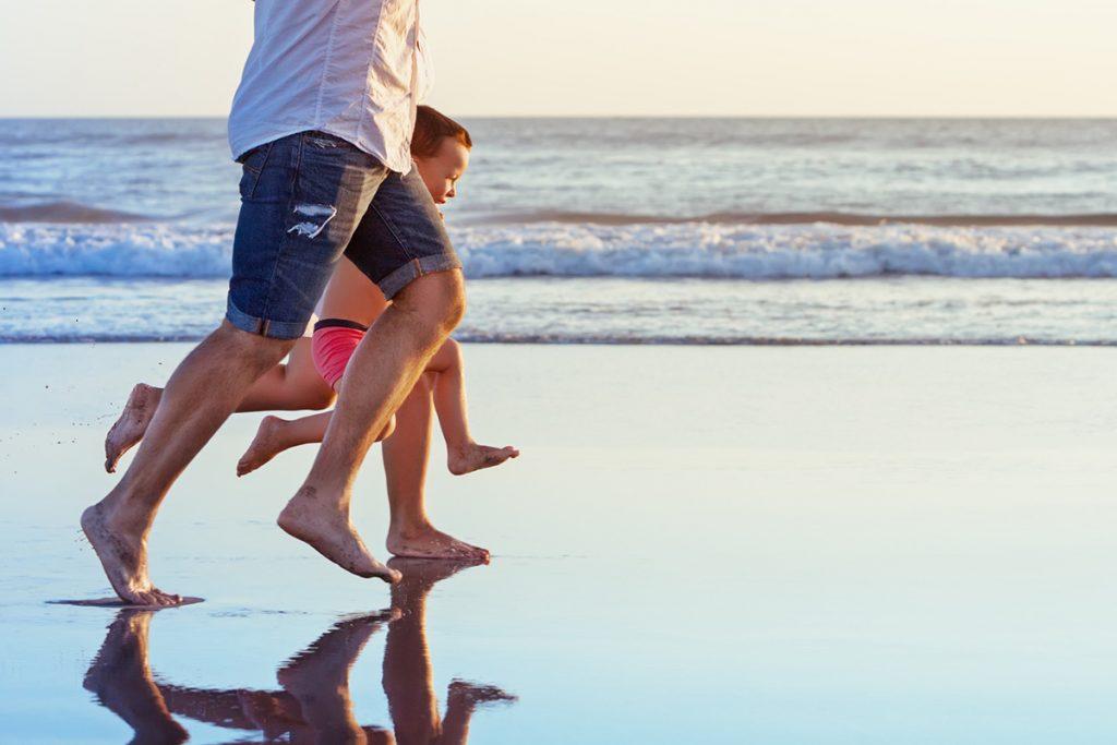 Parents run with son on beach