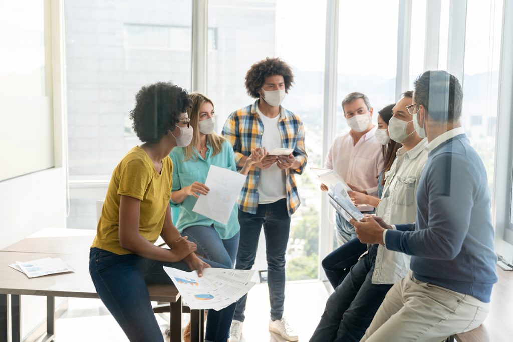 A group having a meeting in masks at an office