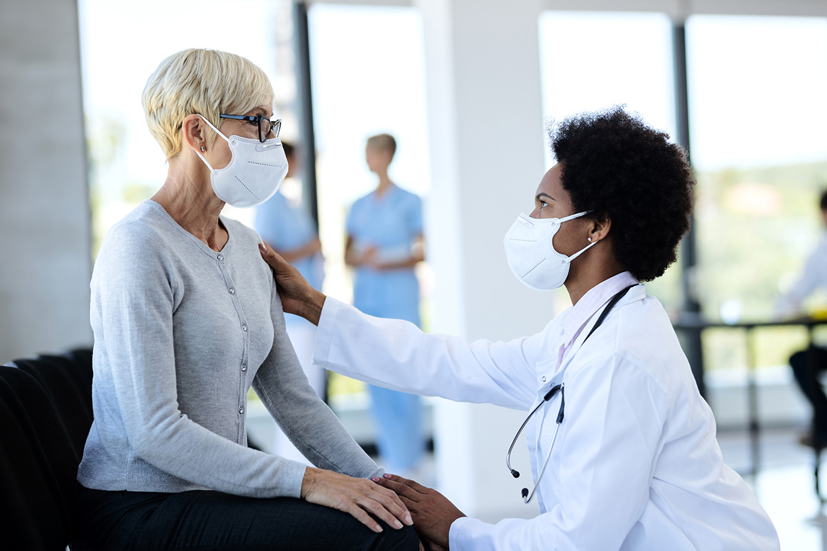Doctor and mature patient wearing protective face masks while talking in waiting room at clinic.