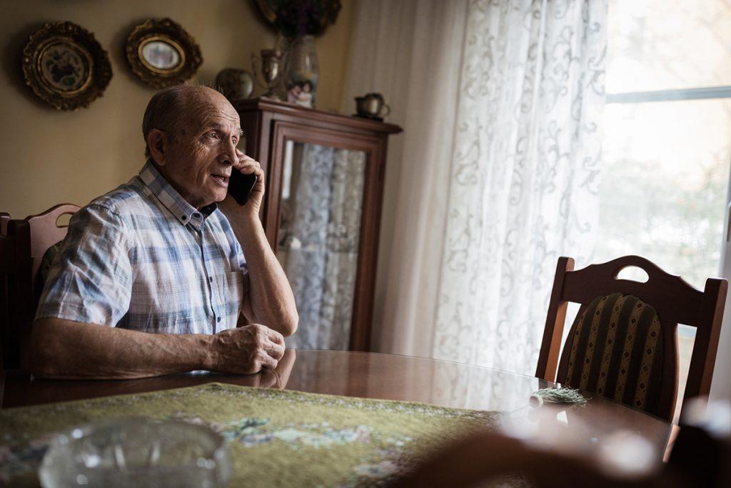 Senior man using mobile phone at home