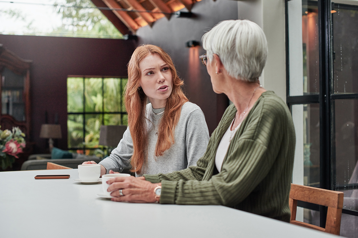 Shot of a young woman having tea and conversation with an older woman
