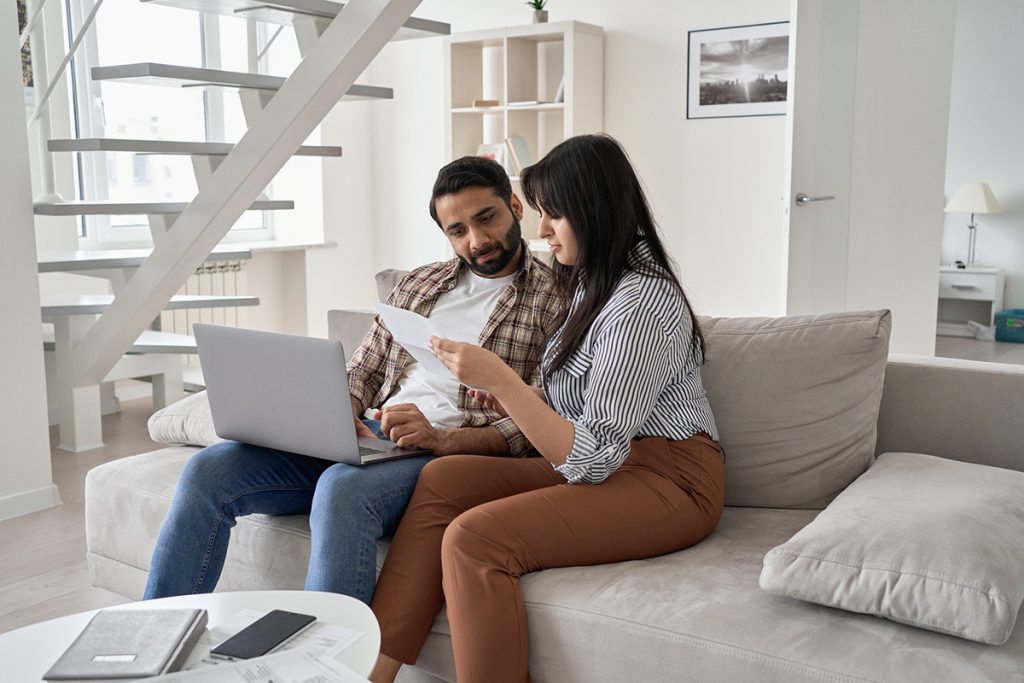 A young couple researches insurance plans online